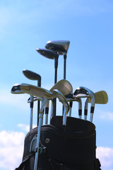 Golf bag with clubs on blue sky background