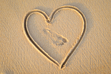 Heart handwrited on golden sand with foot print in it