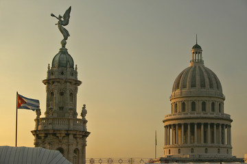Cuban flag at sunrise with the Roofs of Opera House, Dome of the Royal Theater and Capitol, Havana