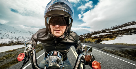 Wall Mural - Biker in helmet and leather jacket racing on mountain serpentine