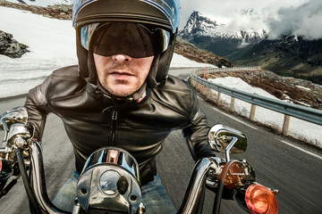 Papier Peint - Biker in helmet and leather jacket racing on mountain serpentine
