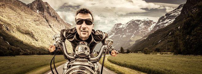 Fototapete - Funny Biker in sunglasses and leather jacket racing on mountain