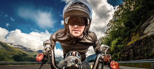 Fototapete - Biker in helmet and leather jacket racing on mountain serpentine