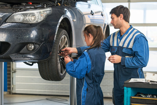 Mechanic teaching an intern in a garage