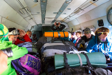 Passengers Inside Cargo Helicopter with Many Backpacks Group of Mountain Climbers Sitting Inside Helicopter with Large Heap of Luggage
