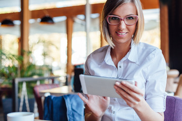 Beautiful business woman uses tablet on coffee break