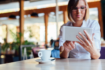 Elegant woman using tablet in a cafe