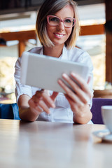 Happy woman using free internet on new tablet in a cafe
