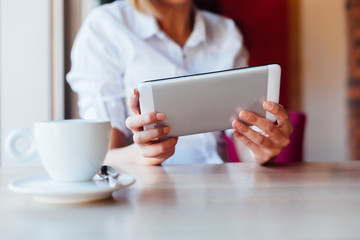 Closeup of woman using tablet on coffee break