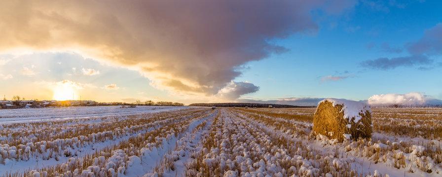 закат на сельском поле с сеном и первым снегом, Россия, Урал