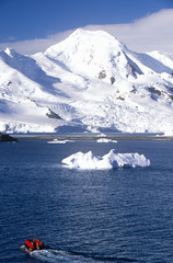 Ecological tourists in inflatable Zodiac boat and glaciers and icebergs near Half Moon Island, Bransfield Strait, Antarctica