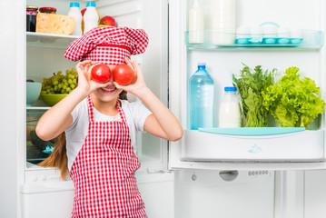 little cook girl holdin tomatoes like eyes