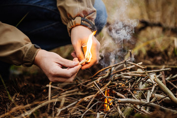 young man kindles a fire in summer wood