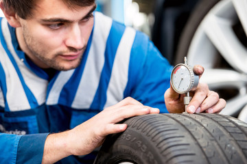 Mechanic, checking the wear on the tread of a tire