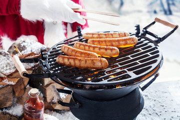 Aluminium Prints Grill / Barbecue Man in Santa outfit grilling sausages
