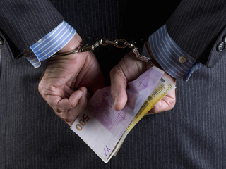Rear view of a businessman in handcuffs with money in his hands