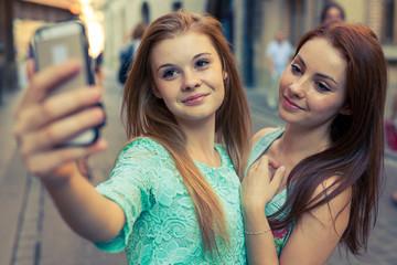 Two pretty girls taking selfie. Urban background. We love selfie