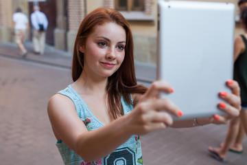 Pretty girls taking selfie. Urban background. Summer day.