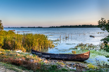 Old boat on the water in the lake among the reeds. Bright sunset landscape on the lake