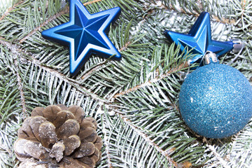 Various decorations for the Christmas and New Year, shiny toys, cones, stars lie on fir branches. Isolated top view