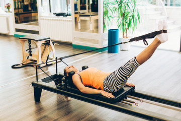 Woman stretching in pilates reformer