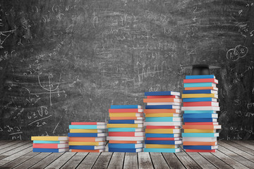 A stair is made of colourful books. A graduation hat is on the final step. Black chalk board with math formulas on the background. Wooden floor.
