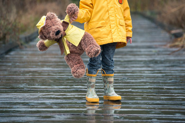 Child and teddy bear in yellow raincoats standing in the rain