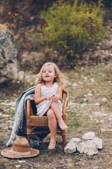 happy little girl in a chair outdoors