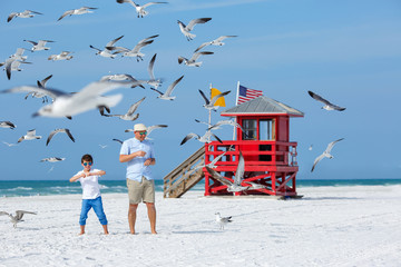 Father and his son feeding seagulls on tropical beach