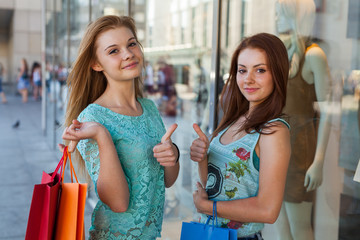Young girls with colorful shopping bags. Season of sales.