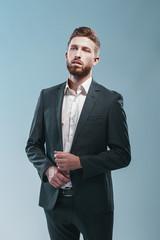 Studio shot of a stylish bearded man in elegant suit, colored tiffany background, isolate