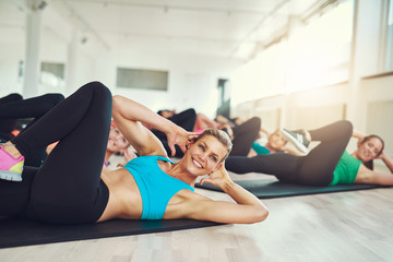 Smiling attractive young woman doing aerobics