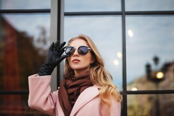 Fashion photo of beautiful young  woman with sunglasses. City lifestyle. Female fashion. Closeup portrait. Beautiful reflection background