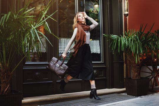Beautiful fashionable young woman running with bag. City lifestyle. Female fashion. Full body portrait.