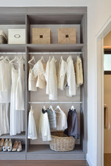 modern closet with row of white dress and shoes hanging in wardr