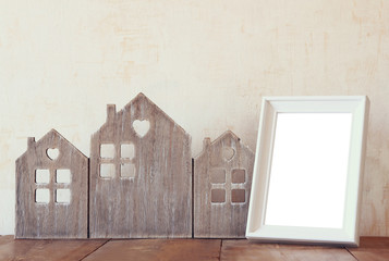 image of vintage wooden house decor, blank frame on wooden table and stars garland. selective focus