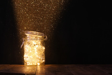 low key and vintage filtered image of fairy lights in mason jar with. selective focus.