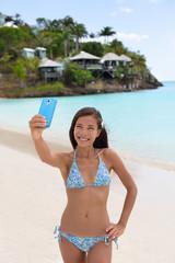 Beach vacation travel woman making smart phone selfie in bikini having fun sharing on social media. Self portrait photo with smartphone on beach. Happy mixed race Caucasian / Asian Chinese woman.