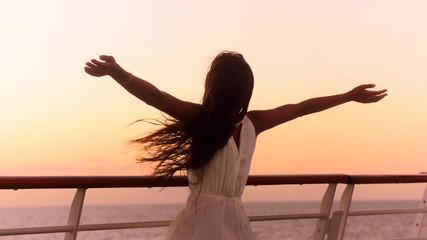 Wall Mural - Cruise ship vacation woman enjoying sunset on travel at sea. Free happy woman looking at ocean in happy freedom pose with arms out. Woman in dress on luxury cruise liner boat.