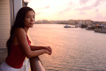 Wall Mural - Cruise ship vacation woman enjoying balcony at sea with beautiful sunset on travel at sea. Relaxed woman enjoying private balcony in stateroom. Asian Chinese / Caucasian woman in dress on cruise liner