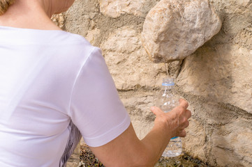 A woman at the water font refilling her water bottle