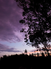 Silhouette Couple of lover standing on the rock top when twiligh