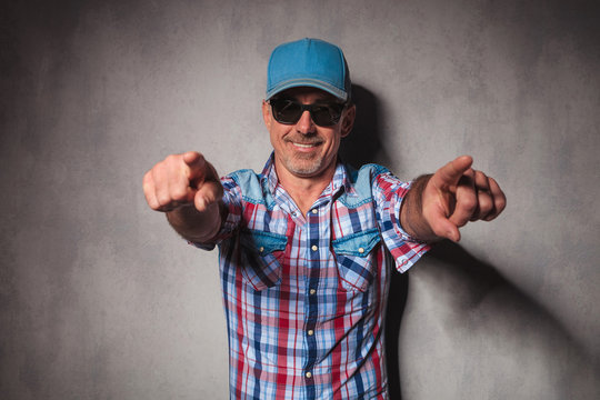 cool mature casual man with trucker hat  pointing his fingers