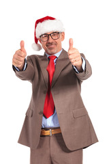 happy senior businessman wearing santa claus hat making ok sign