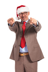 happy aged businessman wearing santa claus cap pointing his fing