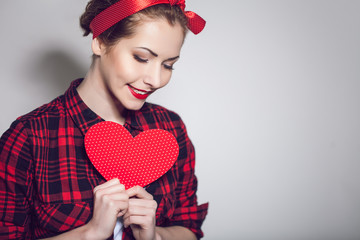 Beautiful young woman with pin-up make-up posing with red heart