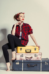 woman sits on retro suitcase
