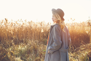 Romantic girl walking in a field in sunset light. Back to camera, winter, autumn life