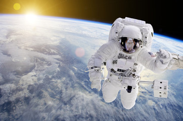 Astronaut in Space, in background our earth an the sun - Elements of this image furnished by NASA