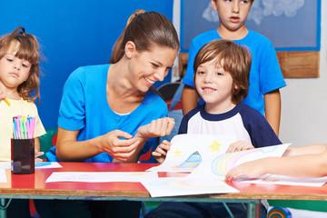 Kinder malen Bilder im Hort mit Erzieherin